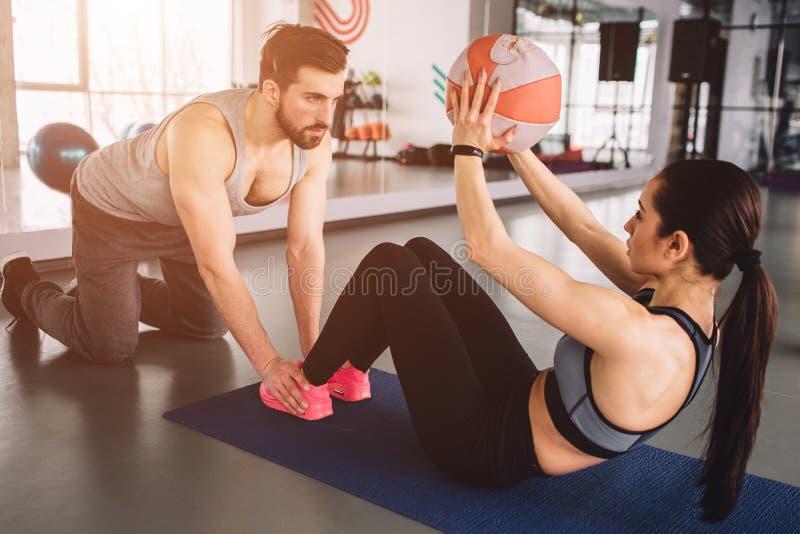 En bild av flickan som gör någon abs, övar med bollen, medan hennes sportpartner rymmer henne ben ner på golvet arkivbild
