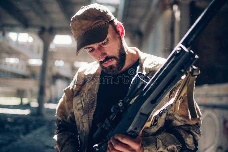 En bild av krigareanseendet i en hangar och att se ner på hans gevär Han gör det ren och förbereder det för att slåss royaltyfria bilder