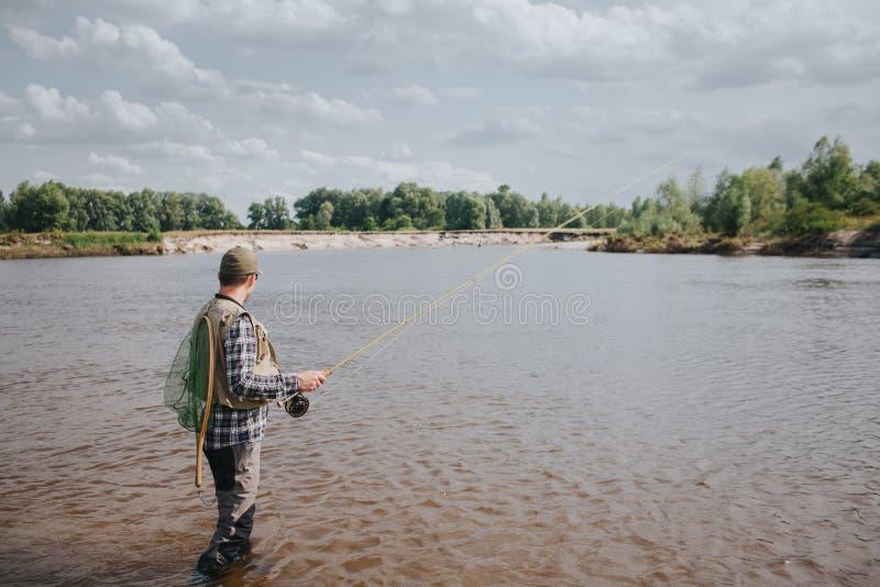 En bild av mananseendet i vatten och fiske Han är den hållande snurret i händer och att se vatten Grabben har fiske royaltyfria foton