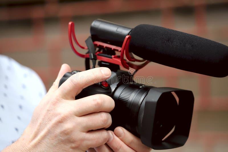 En bild av manliga händer som rymmer en kamera med en mikrofon royaltyfri foto