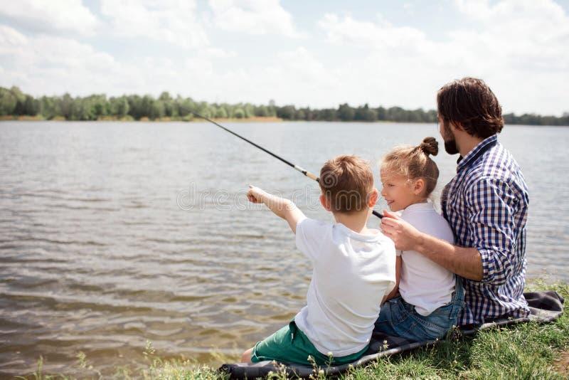 En bild av mannen och hans barn som tillsammans sitter på flodkusten Grabben fiskar, medan hans ungar håller ögonen på på det royaltyfria bilder