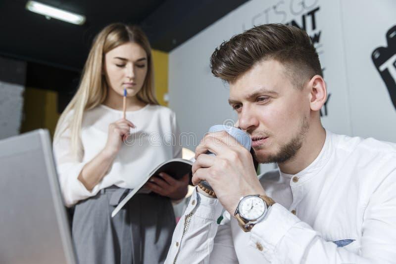 En bild av mannen som framåtriktat ser och talar på telefonen och rymmer en kopp kaffe Han ?r allvarlig Flickan står förutom hono royaltyfri bild