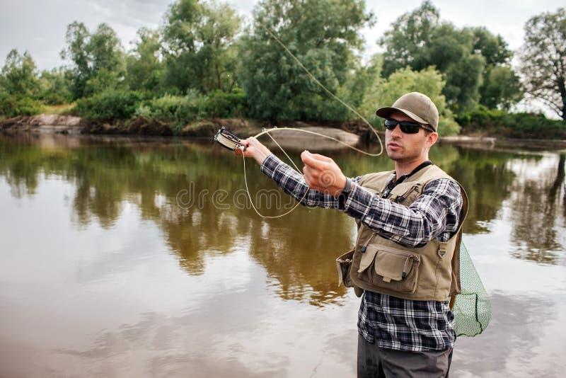 En bild av mannen står, i vatten och att vinka med den klipska stången Han ska fiska Grabben har fisknät på baksidan Han ser royaltyfri bild