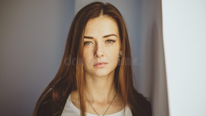 En bild av en modern rödhårig flicka med fräknar Closeupstående som ser kameran royaltyfria foton