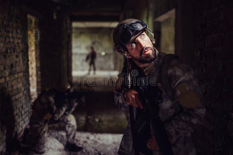 En bild av soldater som står i mörk korridor av tom byggnad Den skäggiga grabben ser upp och rymmer geväret _ royaltyfria bilder