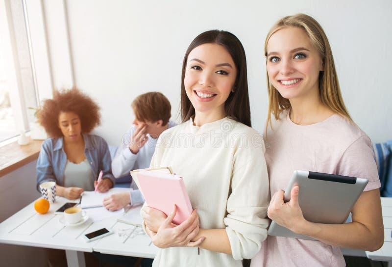 En bild av två härliga asiatiska flickor som står och ler Brunetten rymmer en rosa anteckningsbok, medan den blonda flickan har a royaltyfria bilder