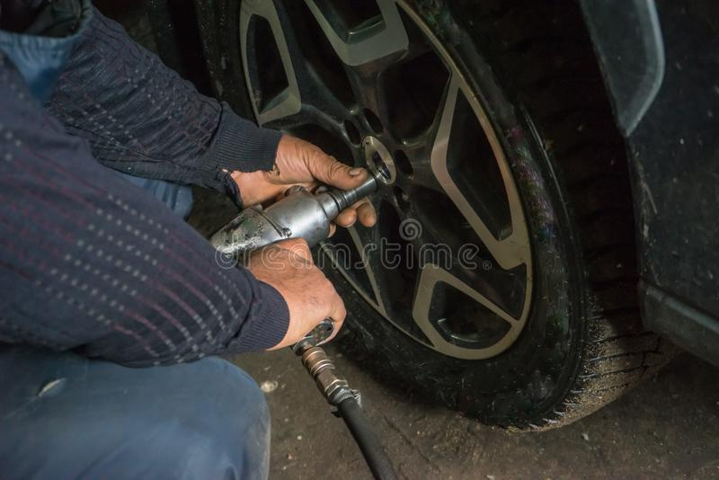 En bilmekaniker ändrar ett gummihjul på ett hjul royaltyfri bild