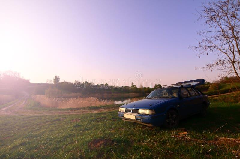En blå bil på en bakgrund av ett lantligt landskap med ett löst rottingfält och en liten sjö Familjen kom att vila på naturen n royaltyfria bilder