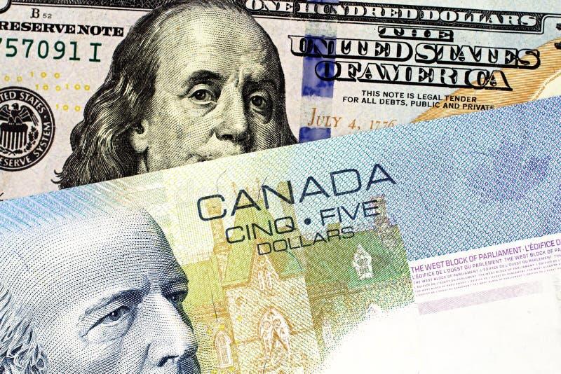 En blå kanadensisk räkning för dollar fem med en amerikansk hundra dollarräkning arkivfoto