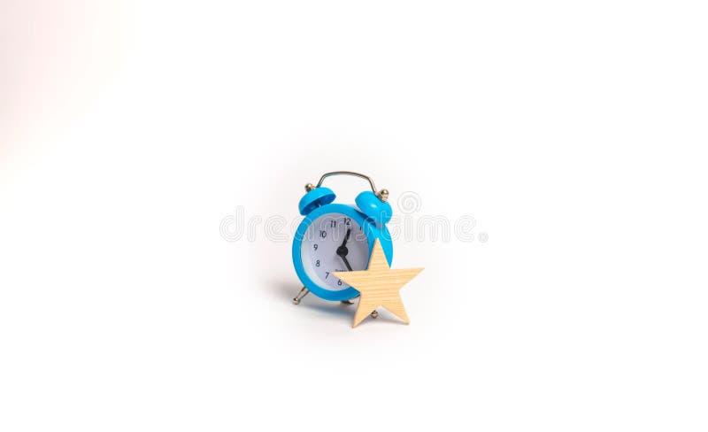 En blå ringklocka och en stjärna Begrepp vip Extra tid behörigheter Specialt erbjudande, inskränkt serie exclusivity Time är peng arkivfoton