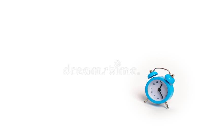 En blå ringklocka på en vit bakgrund Begreppet av tid och planläggningen Forntiden, framtiden och gåvan minimalism fritt arkivbilder
