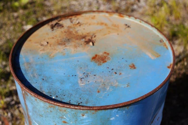 En blå rostig oljatrumma i natur royaltyfria foton