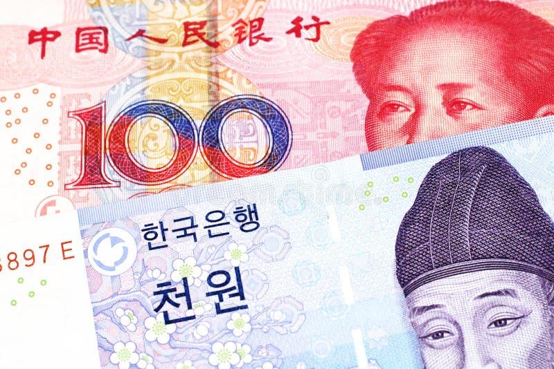 En blå segrad anmärkning från Sydkorea med en yuananmärkning från Folkrepublikenet Kina arkivbild