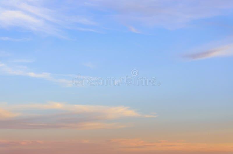 En blå sommarhimmel med rosa färger och vit, försiktiga cirrusmolnmoln arkivbilder