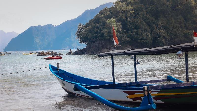 En blå träfartygsegling på stranden royaltyfria bilder