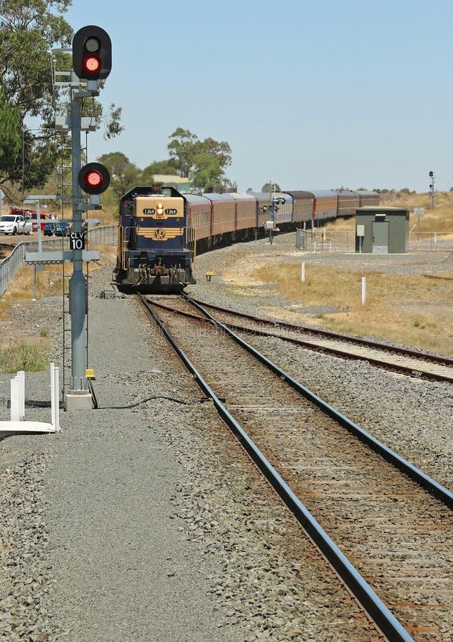 En blått och en gul viktoriansk järnvägT-grupp tappning utbildar, och vagnar att närma sig den Clunes järnvägsstationen arkivfoto