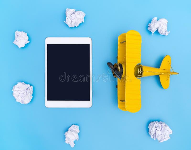 En blanco vacie la tableta con el avión amarillo en el cielo de papel del azul y de la nube para el concepto del viaje imagen de archivo