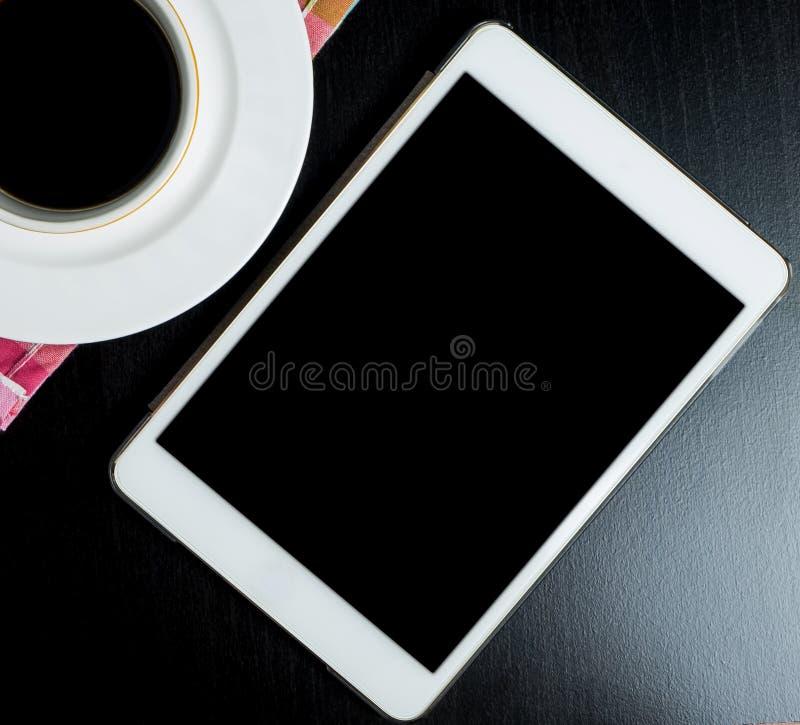 En blanco vacie la tableta con la taza de café en la tabla brillante negra foto de archivo