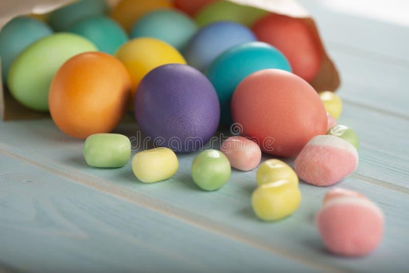En blandning av ljusa färgade fega ägg för påsk i en pappers- påse på en tabell arkivbilder
