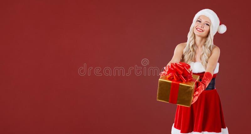 En blond flicka i dräkt för jultomten` s skrattar med en gåva i hennes han royaltyfri bild