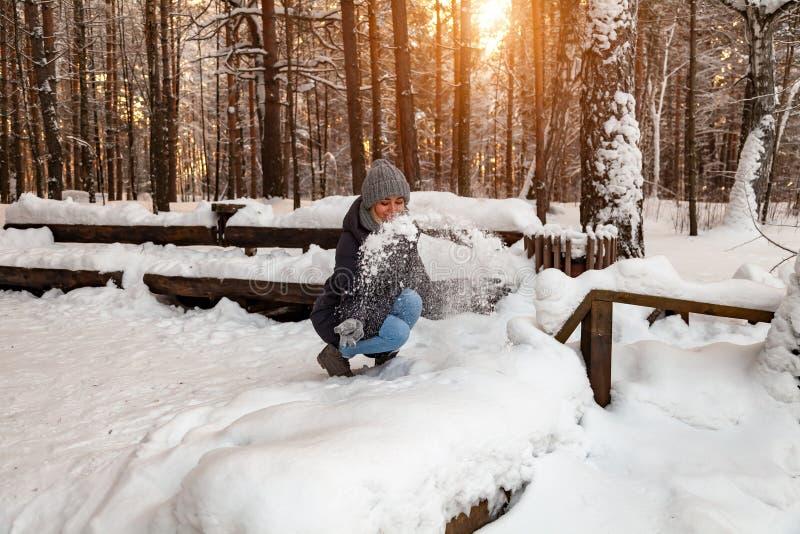 En blond flicka i en grå hatt och handskar och ett vinteromslag squatted framme av en snödriva och att spela med snön som kastar  royaltyfria foton