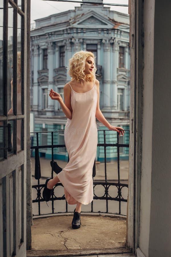 En blond flicka med en cigarett arkivbild