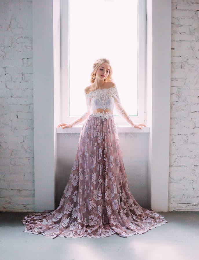 En blond flicka som poserar i en ovanlig lila, snör åt klänningen på en vit bakgrund med ett fönster En lång kjol som klipps av s arkivbild