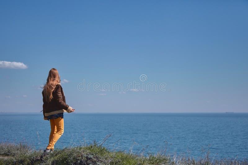 En blond långhårig flicka i gul jeans och ett fårskinnlag promenerar en bana längs en klippa ovanför havet, på en solig vå arkivbilder