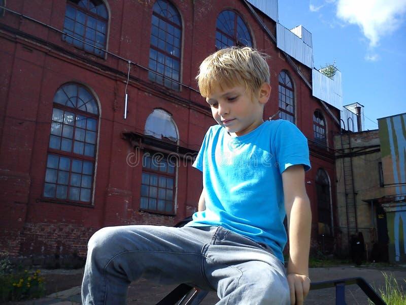 En blond pojke i en blå T-tröja och grå byxor spelar på gatan bredvid en gammal fabrik Barnet klättrade på något fotografering för bildbyråer