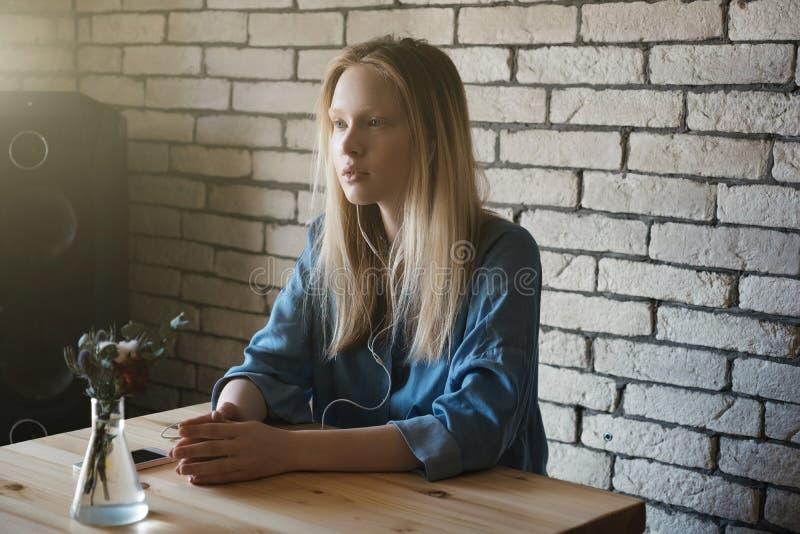 En blondin sitter med hörlurar och ser hänsynsfullt in i avståndet som tillsammans sätter henne jonen för händer tabellen royaltyfri bild