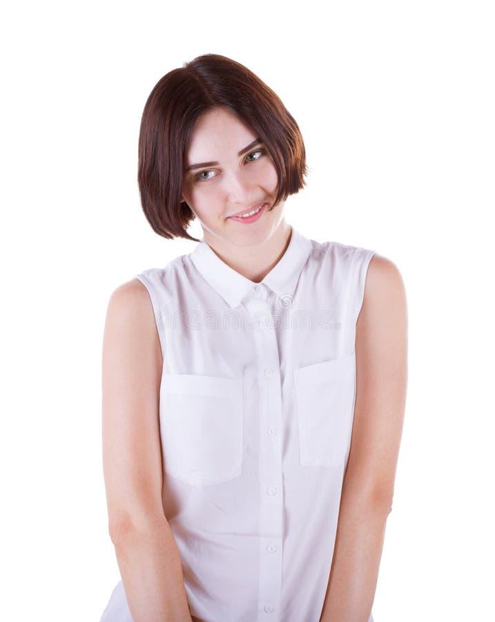 En blyg, romantisk och skämtsam ung kvinna i en vit blus och med ett nätt charmigt leende som isoleras på en vit bakgrundsnärbild fotografering för bildbyråer