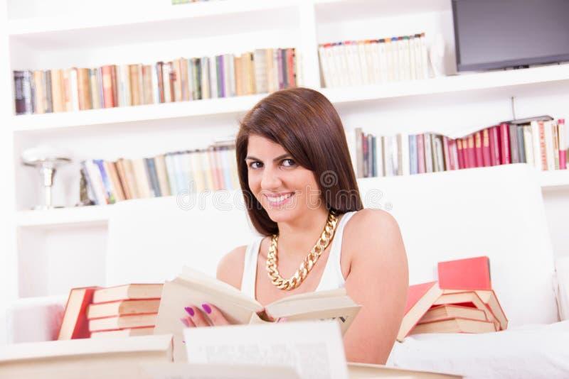En boeken bestuderen lezen en vrouw die glimlachen royalty-vrije stock fotografie
