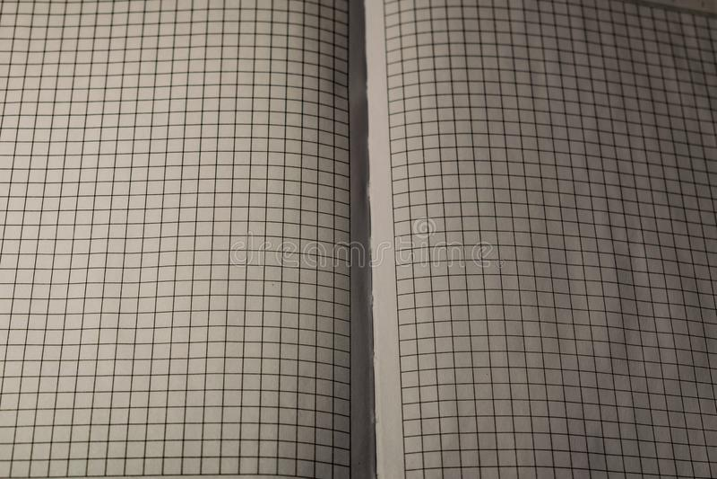 En bok, en anteckningsbok med en rutig modell p? en tr?tabell i olikt poserar R?kningen ?r gr? och mjuk med textur fyrkant royaltyfri fotografi