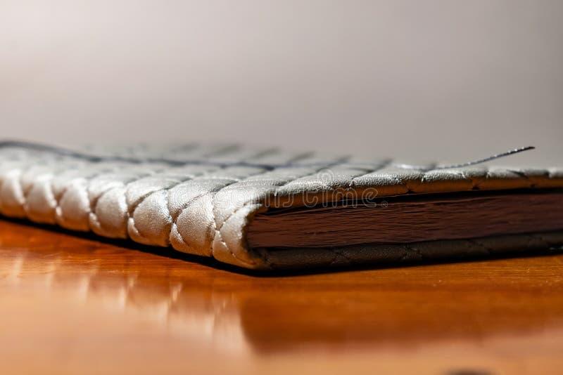 En bok, en anteckningsbok med en rutig modell p? en tr?tabell i olikt poserar R?kningen ?r gr? och mjuk med textur fyrkant arkivbild