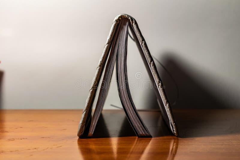 En bok, en anteckningsbok med en rutig modell p? en tr?tabell i olikt poserar R?kningen ?r gr? och mjuk med textur fyrkant royaltyfria foton