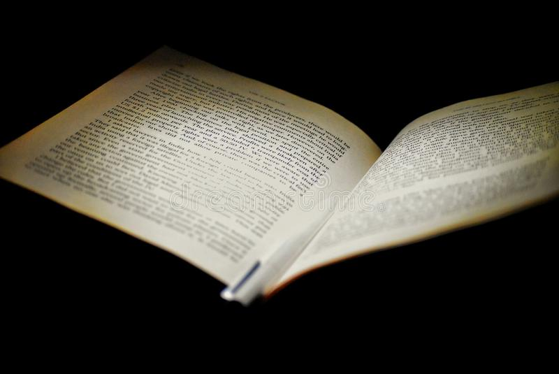 En bok i ett mörkt hörn med ljus på det royaltyfri fotografi