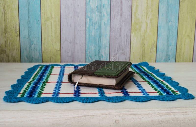 En bok ligger på den färgrika torkduken arkivfoton