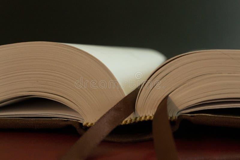 En bokmärke på sidorna av en öppen bok arkivfoto