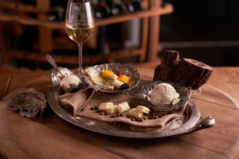 En boll av glass i en gammal glassbunke på ett tappningmagasin med vit choklad och korn av kaffe, fotografering för bildbyråer