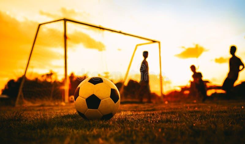 En boll på fältet för grönt gräs för fotbollfotbolllek under det solnedgångstrålljuset och regnet Bild för konturhandlingsport En arkivbilder