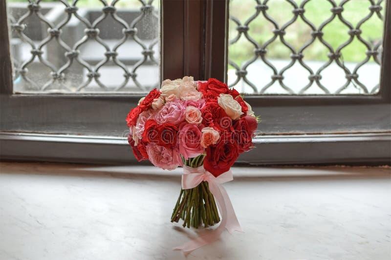 En bröllopbukett med rosor som förläggas på framdelen av ett gammalt klassiskt fönster på en skinande marmorsten royaltyfria bilder