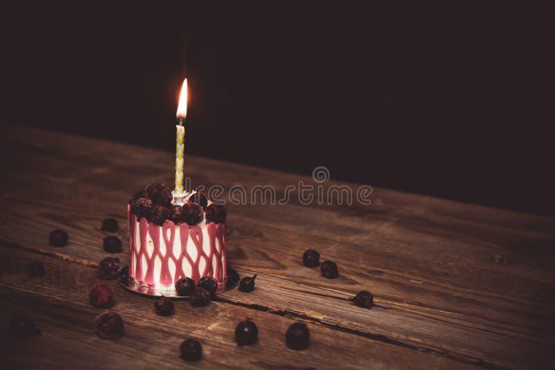 En br?nnande stearinljus i en festlig kakakaka med k?rsb?rsr?da frukter p? en lantlig tr?tabell p? en m?rk bakgrund ?vre kopierin fotografering för bildbyråer