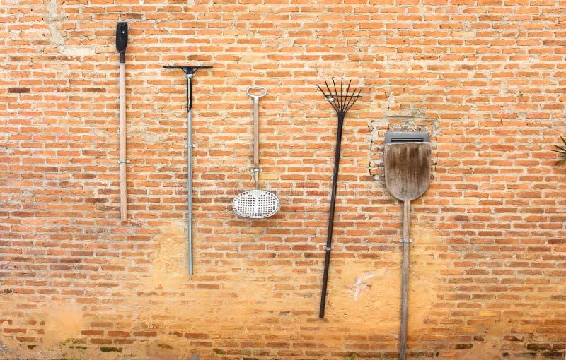 En bra idé att hålla trädgårds- hjälpmedel på den bruna väggen L arkivbild