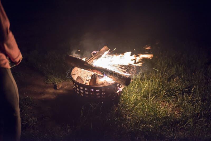 En brand som inom innehålls av en behållare med ett kvinnaanseende bredvid av det arkivbild