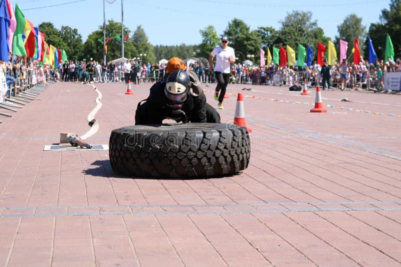 En brandman i en brandsäker dräkt kör och vänder ett stort rubber rullar in en konkurrens för slåss för brand, Vitryssland, Minsk royaltyfri fotografi