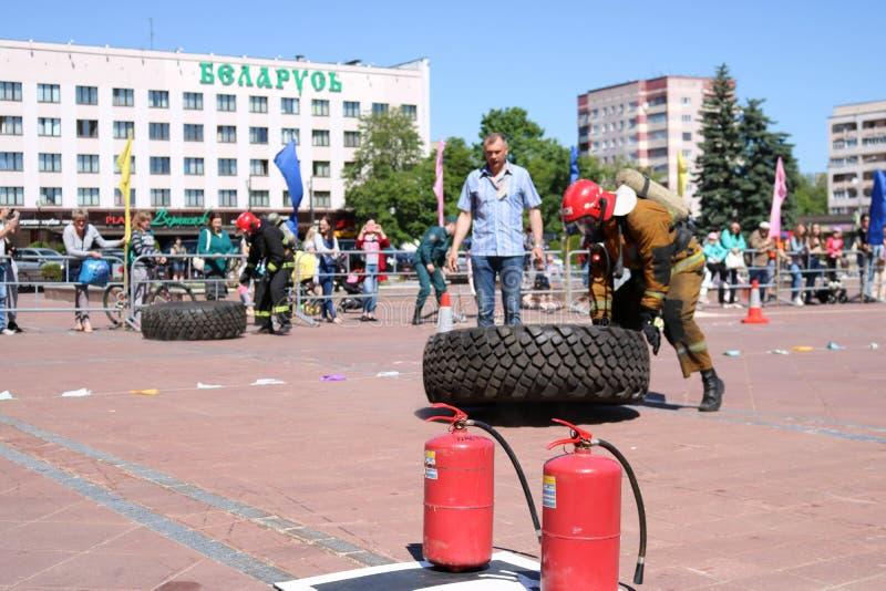 En brandman i en brandsäker dräkt kör och vänder ett stort rubber rullar in en konkurrens för slåss för brand, Vitryssland, Minsk arkivfoton