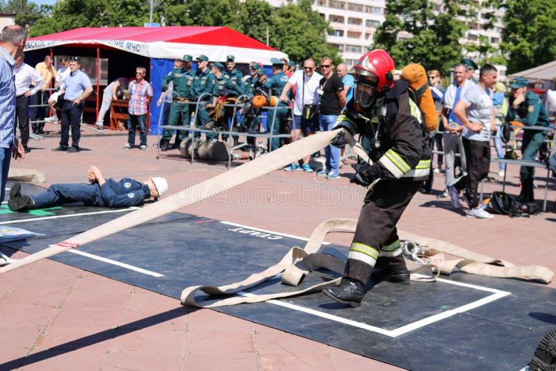 En brandman i en brandsäker dräkt och en hjälm som rymmer en brandslang på en brandsportkonkurrens Minsk Vitryssland, 08 07 2018 arkivfoton
