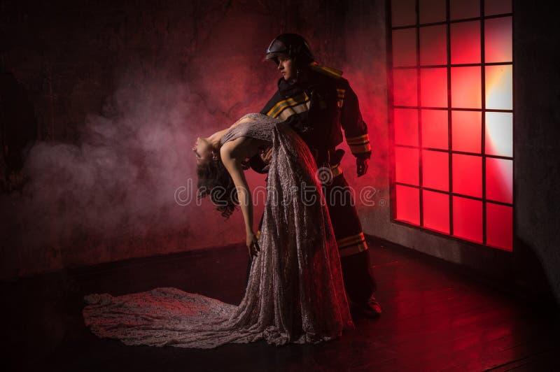 En brandman med härliga kvinnor i lång klänning arkivbild