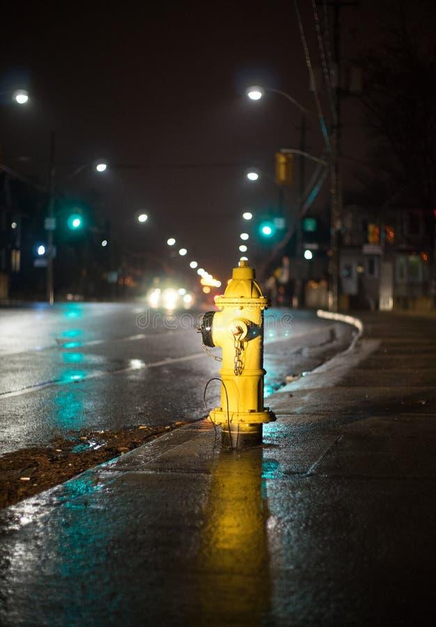 En brandpost exponerad av bilbillyktor royaltyfria foton