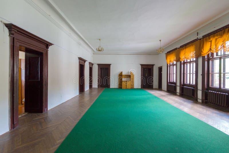 En bred korridor ledas till av en grön bana och parkett med många dörrar till andra rum och stora fönster till gatan arkivfoto